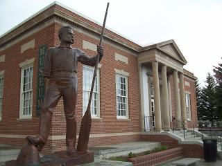 One armed John Wesley Powell stands in front of the Museum, which was the originally a Post Office