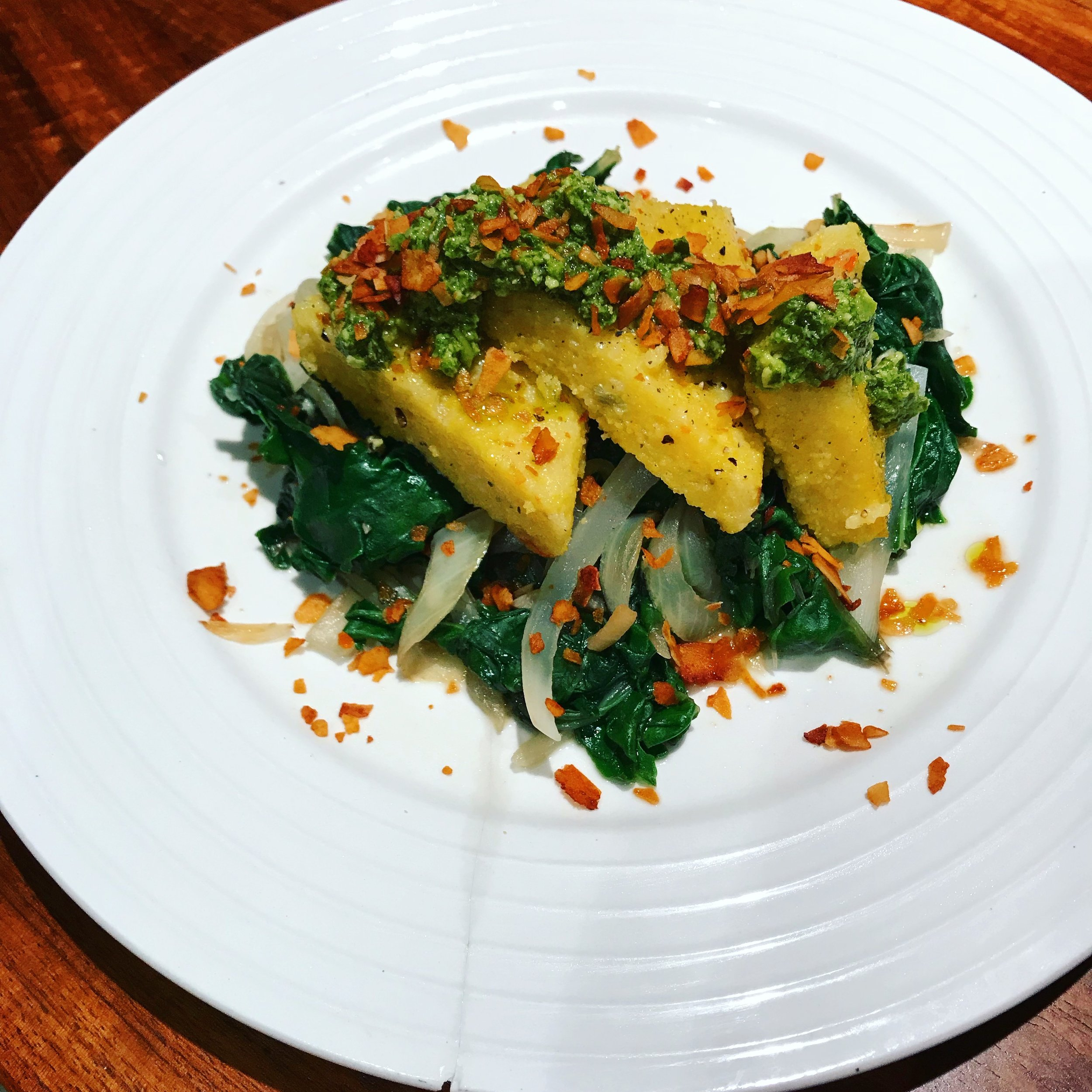 """Polenta triangles I fried in a bit of oil, put them on top of more greens and topped with my favorite coconut bacon """"Faken Bacon"""". What you can't tell from this picture is that they did not have a even golden-crisp to them. Improvement was definitely needed!"""
