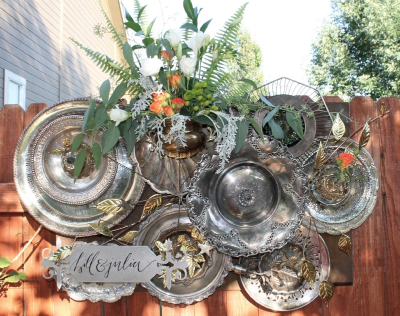 Backdrop for the wedding: platters, glass, brass, flowers and sign.  Welding practice comes into play along with floral design.
