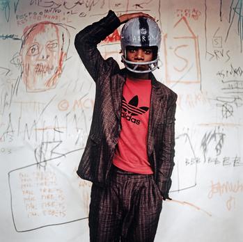 Jean-Michel Basquiat wearing an American football helmet, 1981 | Photo: © Edo Bertoglio, courtesy of Maripol. Artwork: © The Estate of Jean-Michel Basquiat.