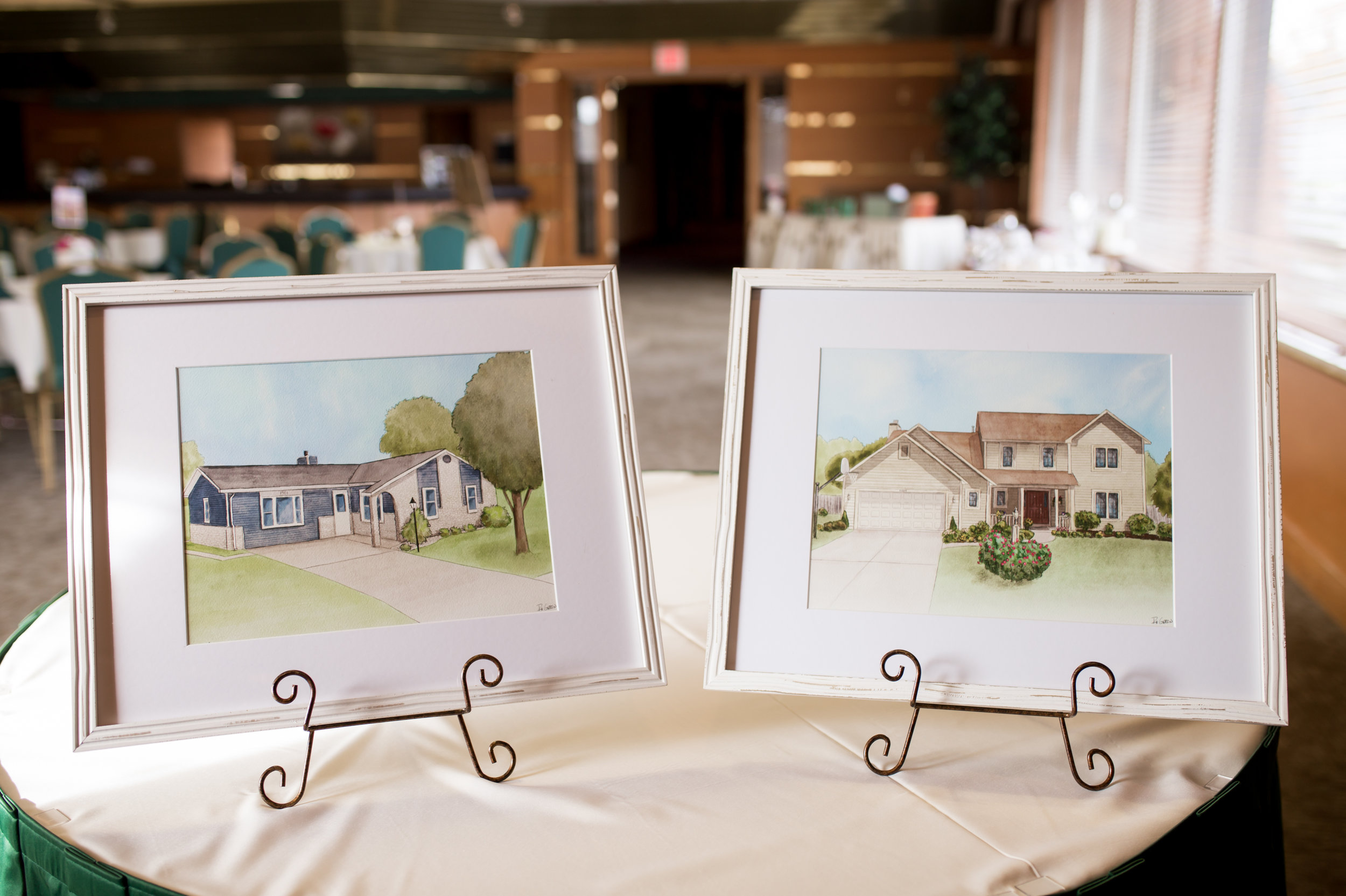 Client had portraits of their childhood homes created as thank you gifts to their parents at their wedding. Client provided photo of the artwork framed and matted on display at their reception.