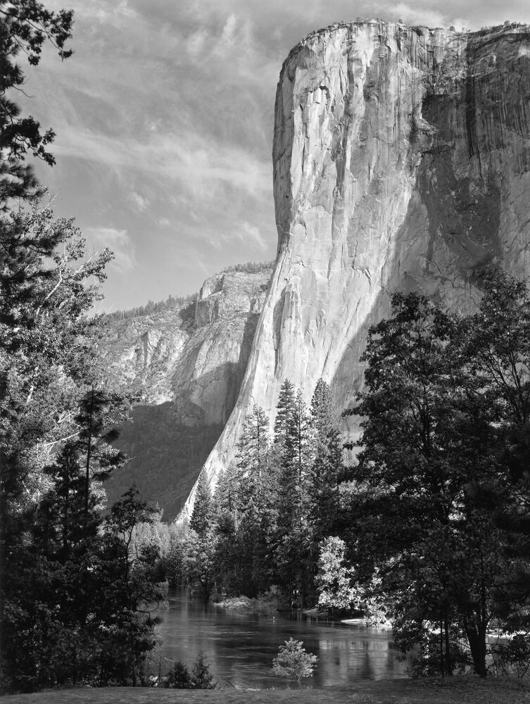 "EL CAPITAN as shot by ANSEL ADAMS captured in 1952.   Ansel Adams made this image around 1952 with an 8"" x 10"" view camera. El Capitan is the largest exposed granite face in the world, drawing climbers from around the globe. Thanks to Adams' work, it's also a magnet for photographers and this image has long been a favorite of the Adams family. During his career, he took many images of El Capitan's dramatic face, notably one of his first known photographs taken in 1916 on his first trip to Yosemite . Using a Kodak #1 Box Brownie, he offered an early hint at the visualization that would later become his hallmark, framing the pale granite face with leafy trees in the foreground to downplay the overwhelming size of El Capitan. After that early photograph, Ansel Adams returned to El Capitan over and again photographing it in every time, season, and light he could."