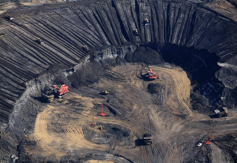 Mining equipment scrape tar sands out of the boreal forest of Alberta, Canada.