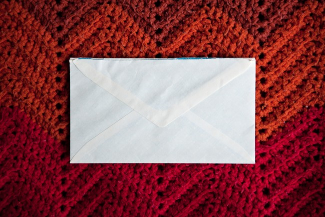 white envelope on blanket of red yarn