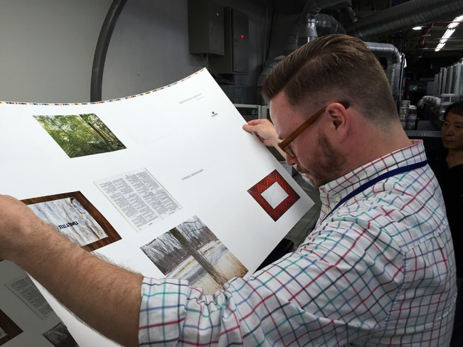 man looking at a large white sheet with images of Northwoods Journals by Kurt Simonson, printed by the bigger dot