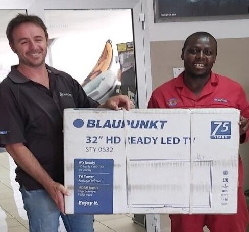 Craig Eastcroft, Downtown Manager, presents the TV to a smiling Dicto Mulunda