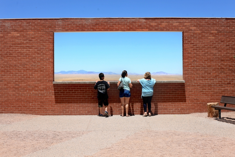 "Ethan Arbelo, Maria Maldonado and Lea Sellwood, left to right, look out onto the desert at a meteor impact site on June 25, 2013, just outside of Winslow, Ariz. With Ethan's help, Maria put an itinerary together for a cross-country road trip so Ethan could see faraway places. They invited Lea, a 9-year-old friend with leukemia they knew from All Children's Hospital in St. Petersburg and were on their way. ""This is a beautiful view, ain't it?"" Ethan said. ""B-E-A-U-tiful."""