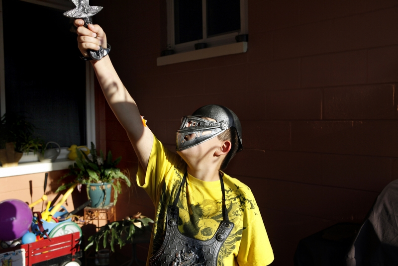 "Ethan Arbelo, 11, plays in the backyard of a friend's home who also has terminal cancer on April 10, 2013 in St. Petersburg, Fla. Ethan often found himself imagining superhero scenarios. ""I like them so much because, just as someone is about to die, they swoop in and save them,"" he said."