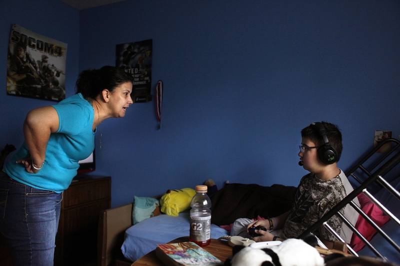 "While playing video games, Maria Maldonado yells at Ethan Arbelo, 12, for not putting more effort into using his left arm, which had begun to paralyze from swelling in his brain on December 2, 2013, in Lehigh Acres, Fla. As Ethan's sole caregiver, Maria struggled at times with managing her stress and finding a balance of tough love with Ethan as his condition worsened. ""This is his battle and he needs to fight with everything in his power, no matter how hard it gets,"" Maria said."