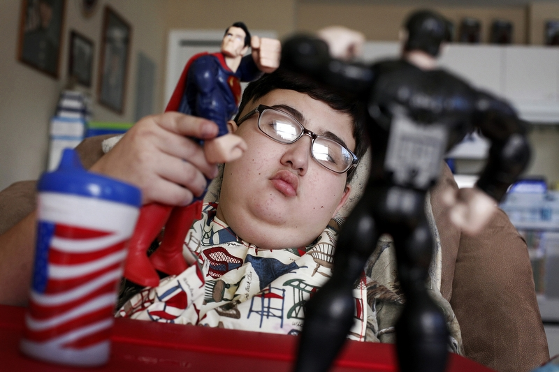 "Too weak to walk on January 17, 2014, Ethan Arbelo, 12, plays with Superman action figures in a reclining chair where he spends most of his days in Lehigh Acres, Fla. ""It's heartbreaking watching your child revert,"" Maria said."