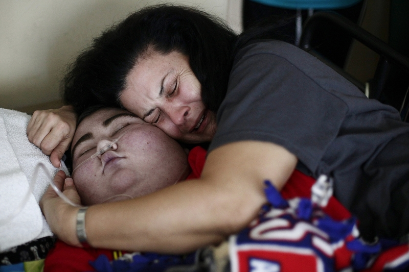 "Maria Maldonado cries hugging Ethan Arbelo, 12, as he transitions into death on July, 3, 2014, in Lehigh Acres, Fla. ""In those last minutes when you know your son is taking those last breaths, all you're doing is praying for death for you too because you can't imagine life without your baby,"" Maria said."