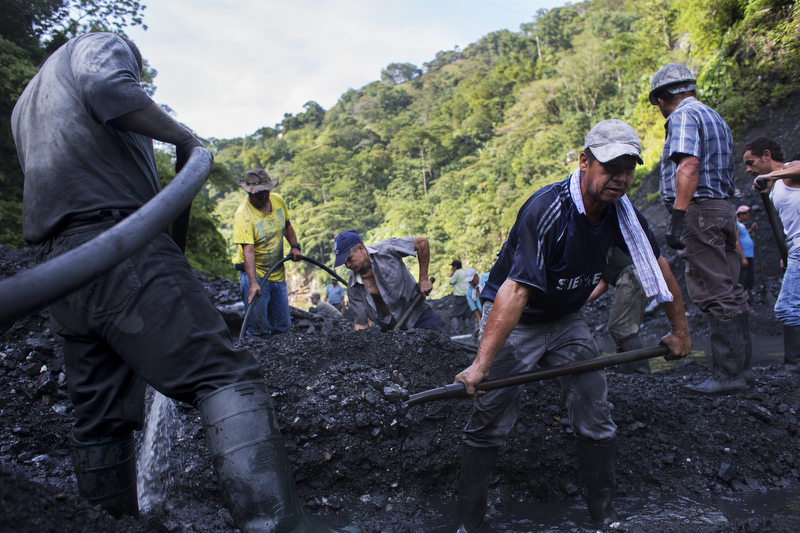 Carlos Sanchez, front left, and Jose Vicente Ico, front right, dig through mined rubble just outside the Minería Texas Colombia plant with hopes of finding gems in Muzo, Colombia, on July 26, 2015. When MTC was awarded the concession to exploit the main emerald mine in the region it limited the access for informal miners to dig through the castoff soil. The company invested millions in the production, allowing them to filter out more emeralds, but leave fewer scraps.