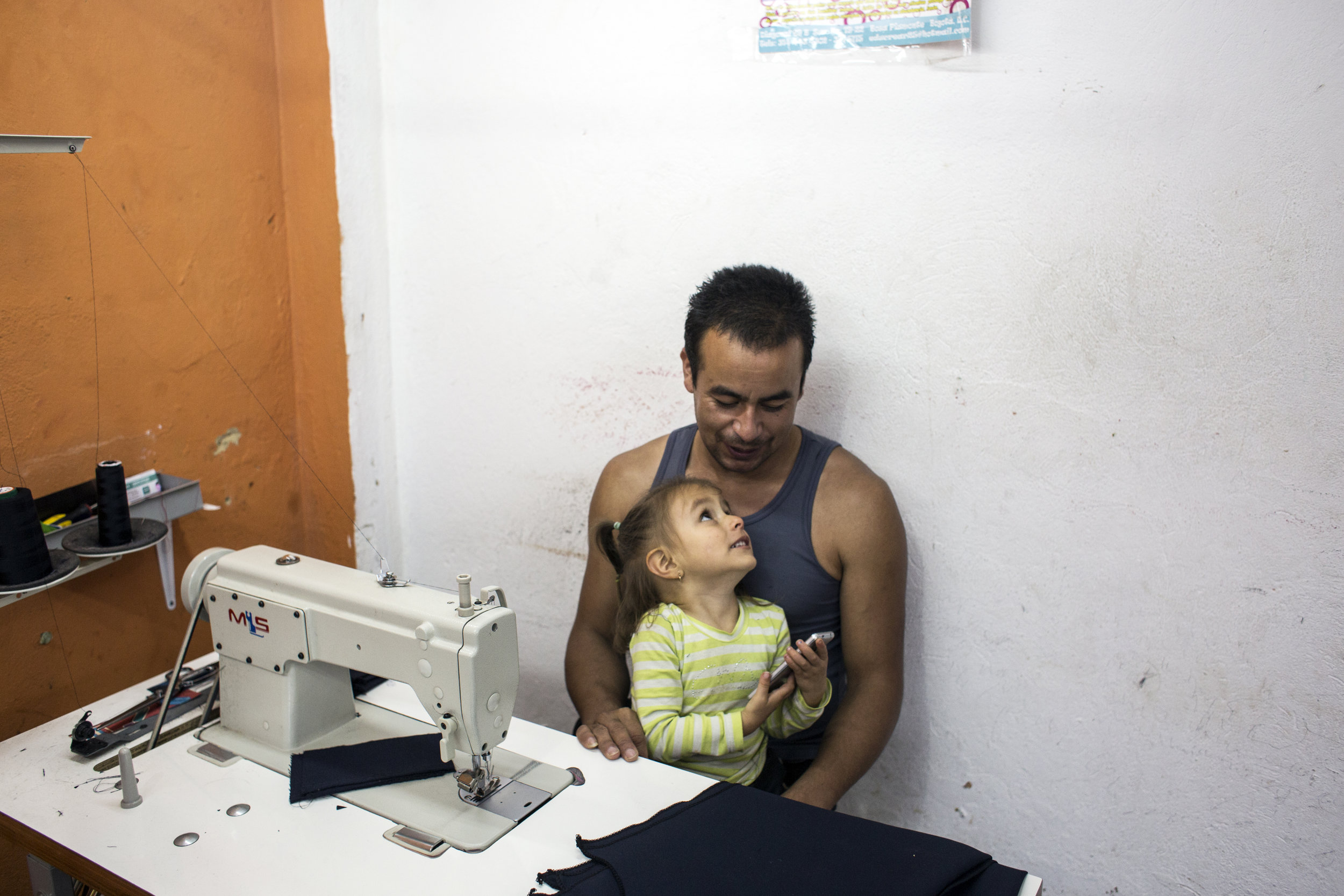 Milton Hernandez, 33, sits with his daughter, Dana Sofia Hernandez, 3, while at his clothing business, where he sews pants and jackets for a brand on September 21, 2016, in Bogotá, Colombia. Hernandez was 19 when he joined the FARC and demobilized 10 years later, after losing a leg to a grenade. He says he had a rough start integrating back into society but is happy he is financially stable and working for something he enjoys.