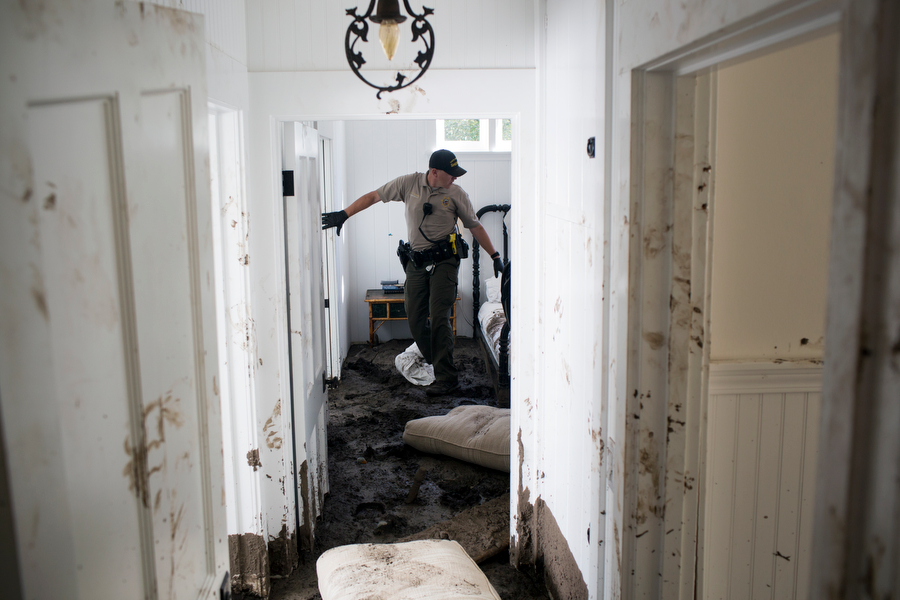 Senior deputy Dennis Thomas leads survivors of a devastating mudslide through a home to search for belongings in Santa Barbara, Calif. on January 26, 2018.