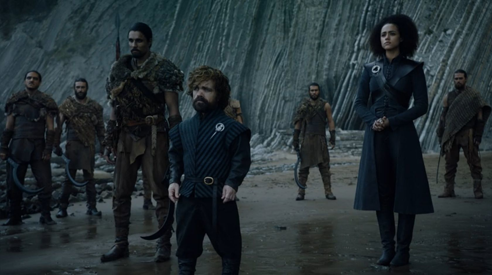 """Greeting Jon Snow at Dragonstone. Missandei, """"the queen's most trusted adviser"""" is placed behind Tyrion in order of precedence and on the same plane as a Dothraki warrior. Her clothes strongly reference her queen's latest sartorial statements crossed with her warrior lover Grey Worm's.She has a status brooch for House Targaryen, a circle of three dragons, while Tyrion wears the brooch of a Hand, the senior advisor to a ruler. She holds the position of a Chamberlain but not necessarily the ruler's most trusted advisor."""