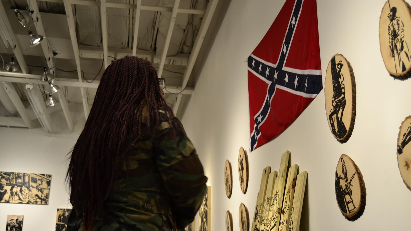 1493047007644-A-young-woman-examines-Lawrence-Mathews-piece-_Worst-than-Slavery_-at-Ancestors-Remind-Us-I-hosted-by-The-CLTV_.jpeg
