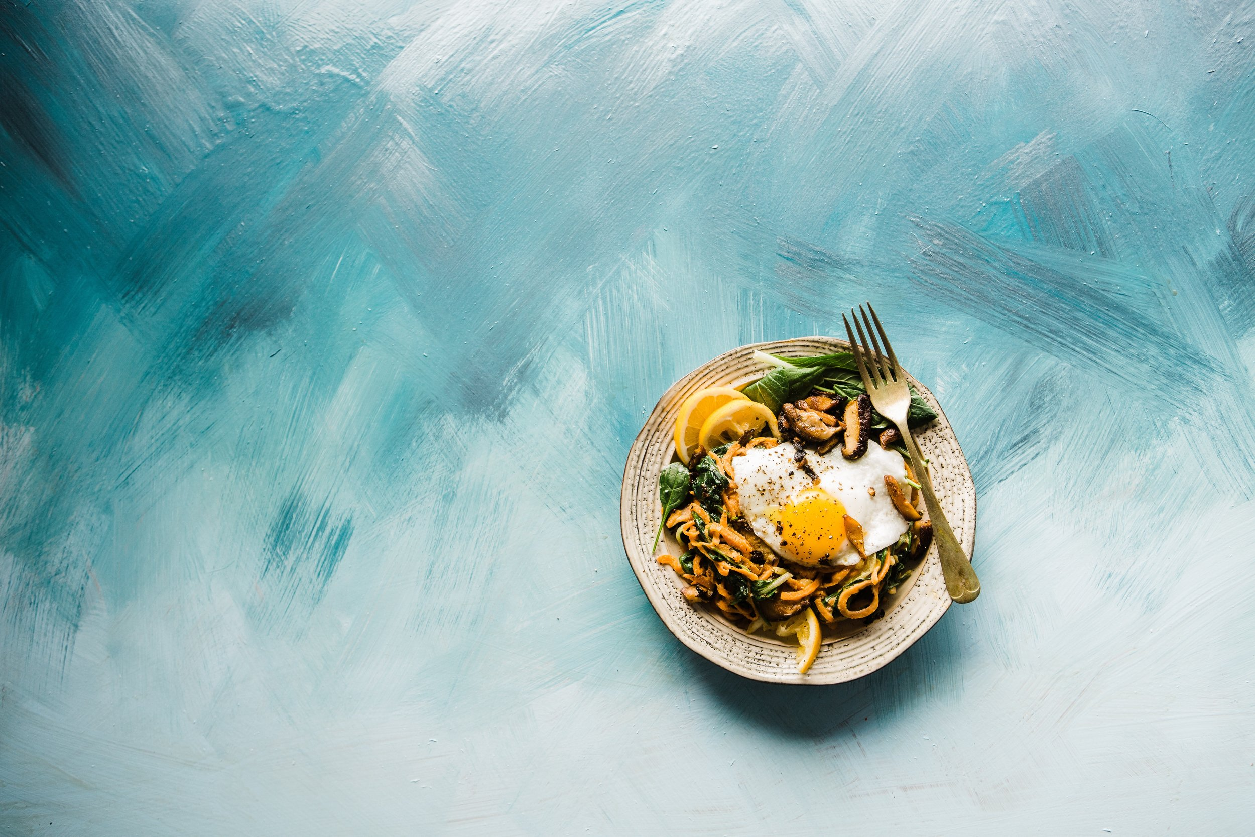 [Image: Round plate with egg, noodles, oranges, and vegetables on a turquoise and grey background.]
