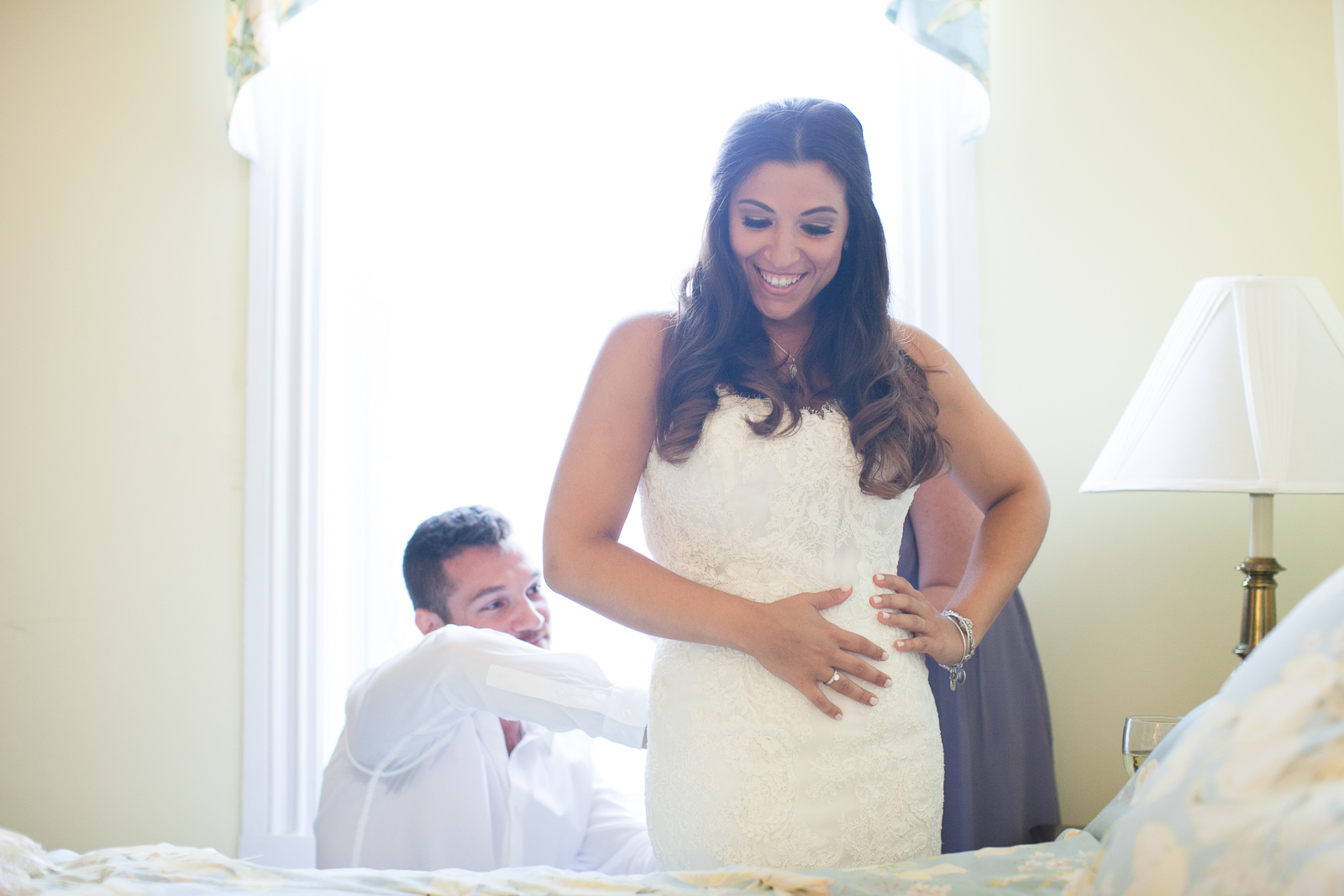 The bride putting on her dress before the ceremony