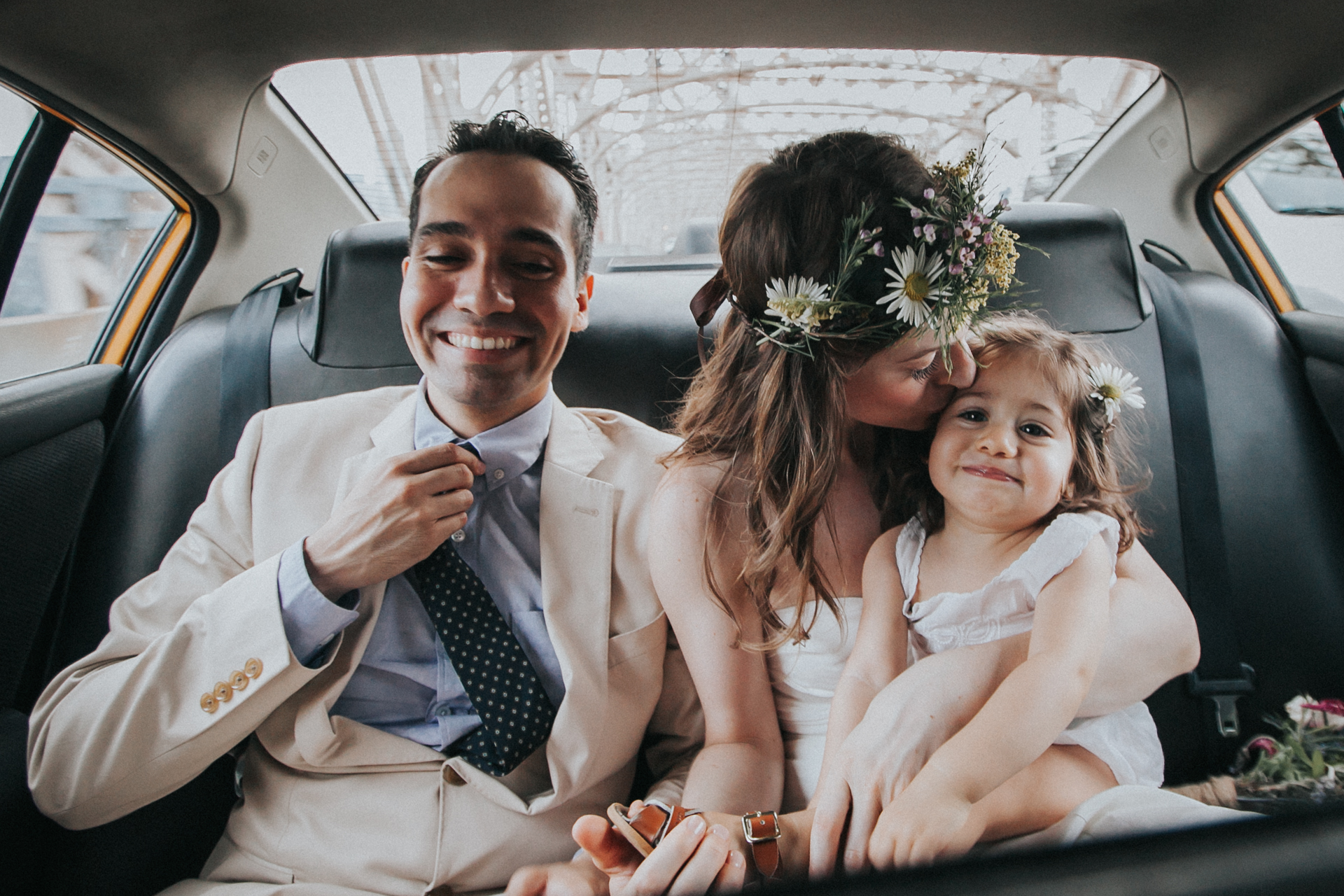 The bride and groom with their daughter, on the way to their ceremony via taxi