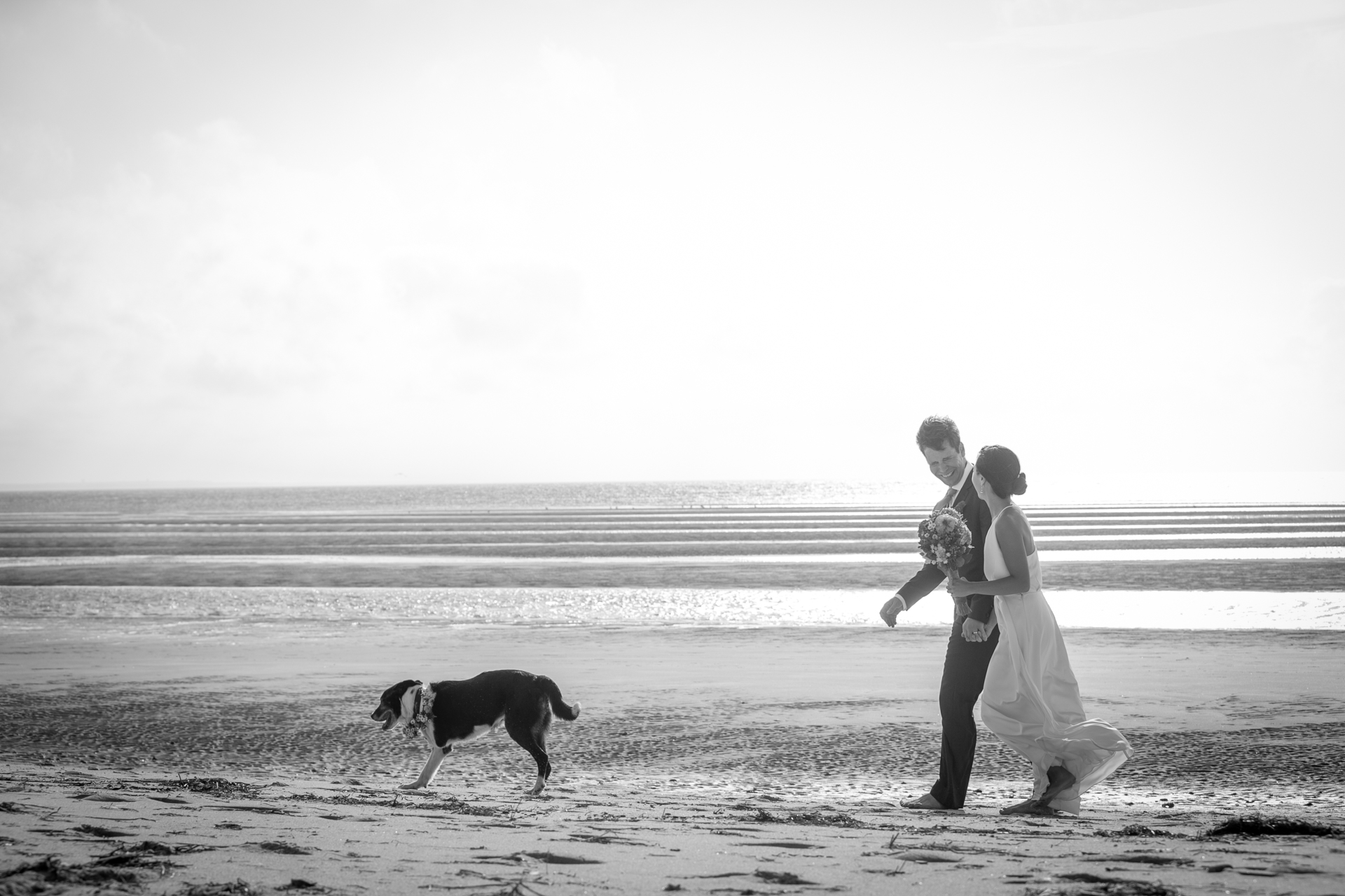 The bride and groom take a leisurely stroll on their way to the ceremony with their dog