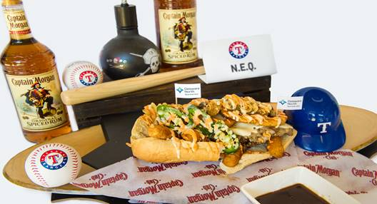 The N.E.Q Sandwich-  Philly cheesesteak topped with provolone cheese, fried jalapeno slices, onion rings, waffle fries, fried mozzarella and white queso.Served with Captain Morgan dipping sauce.