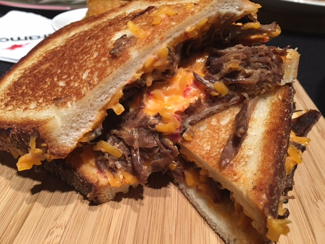 Texas short rib grilled cheese - Seasoned pulled short rib, house made pimento cheese on Texas toast and served with fried pickles.