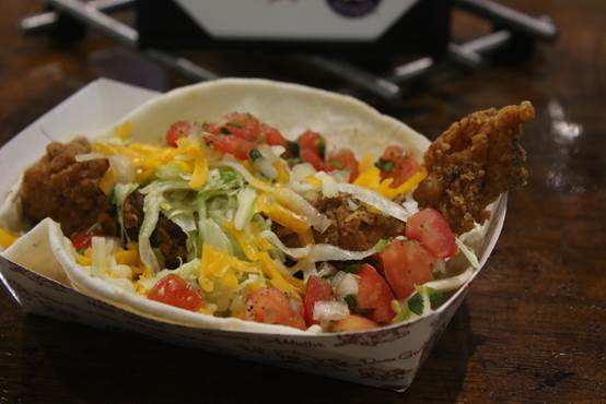 Torchy's Trailer Park Taco – a friend chicken, green chilies, lettuce, pico de gallo and cheese on a flour tortilla with poblano sauce.