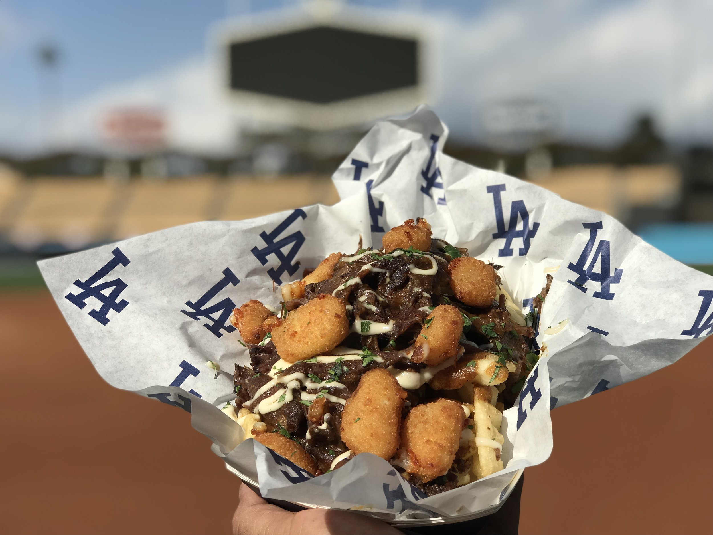 SHORT RIB WAFFLE FRIES     Braised short ribs, red wine reduction sauce over waffle fries topped with crispy cheese curds located at   Bud & Burgers on Field level (section 47) & Top Deck Dogs Too on Top Deck (section 4)
