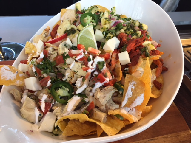Nacho of the Game - Corn tortilla chips, homemade cheese sauce, pork al pastor, spicy chimichurri, pineapple salsa and fresh jalapeno.