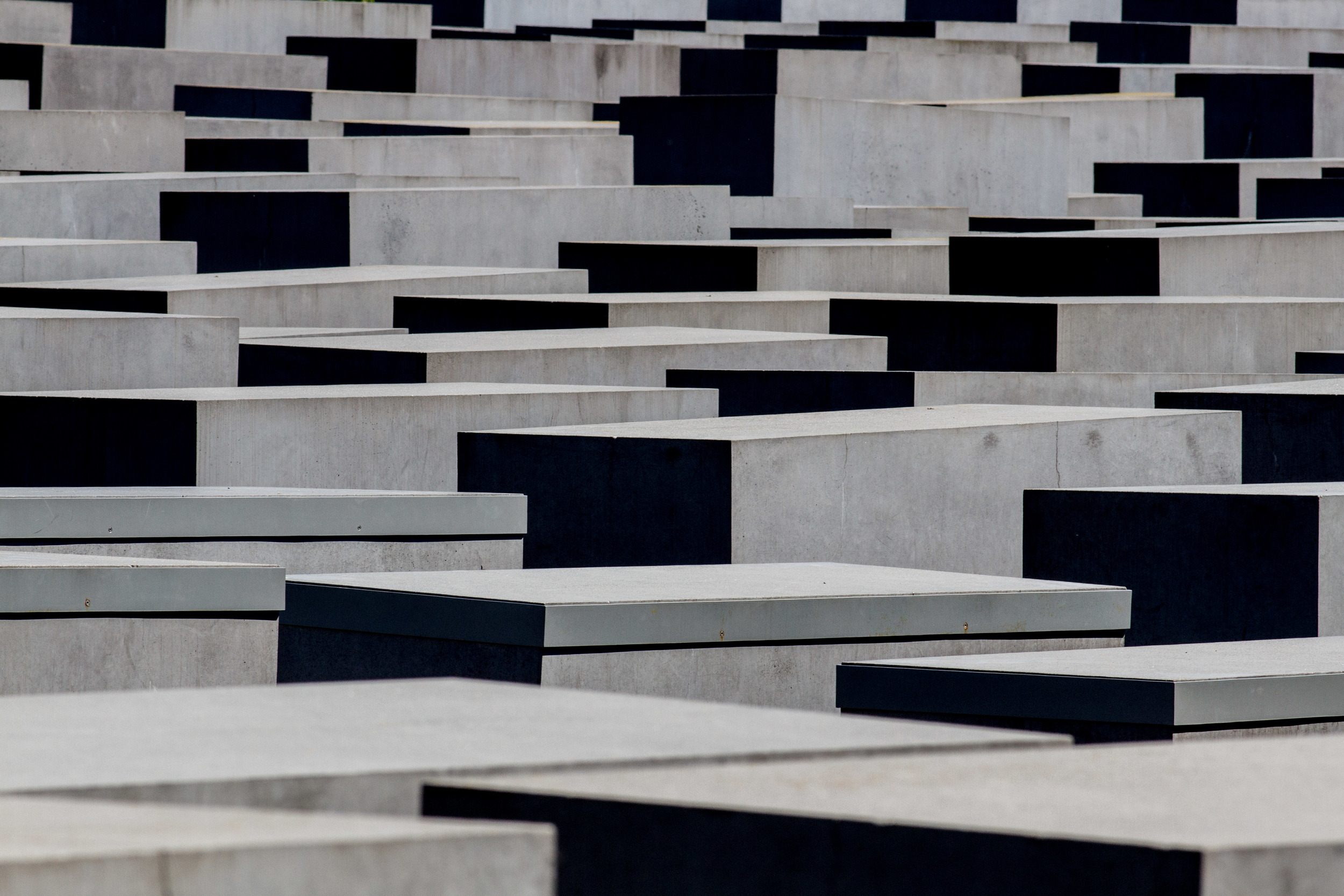Field of Stelae known as the Holocaust Memorial by Peter Eisenman. The austerity of the structures, their labyrinth and repetition are powerfully emotive yet very understated. A separate exhibition centre provides documentary archive and layers of story that are only hinted at by the memorial itself. Image by John Dawson