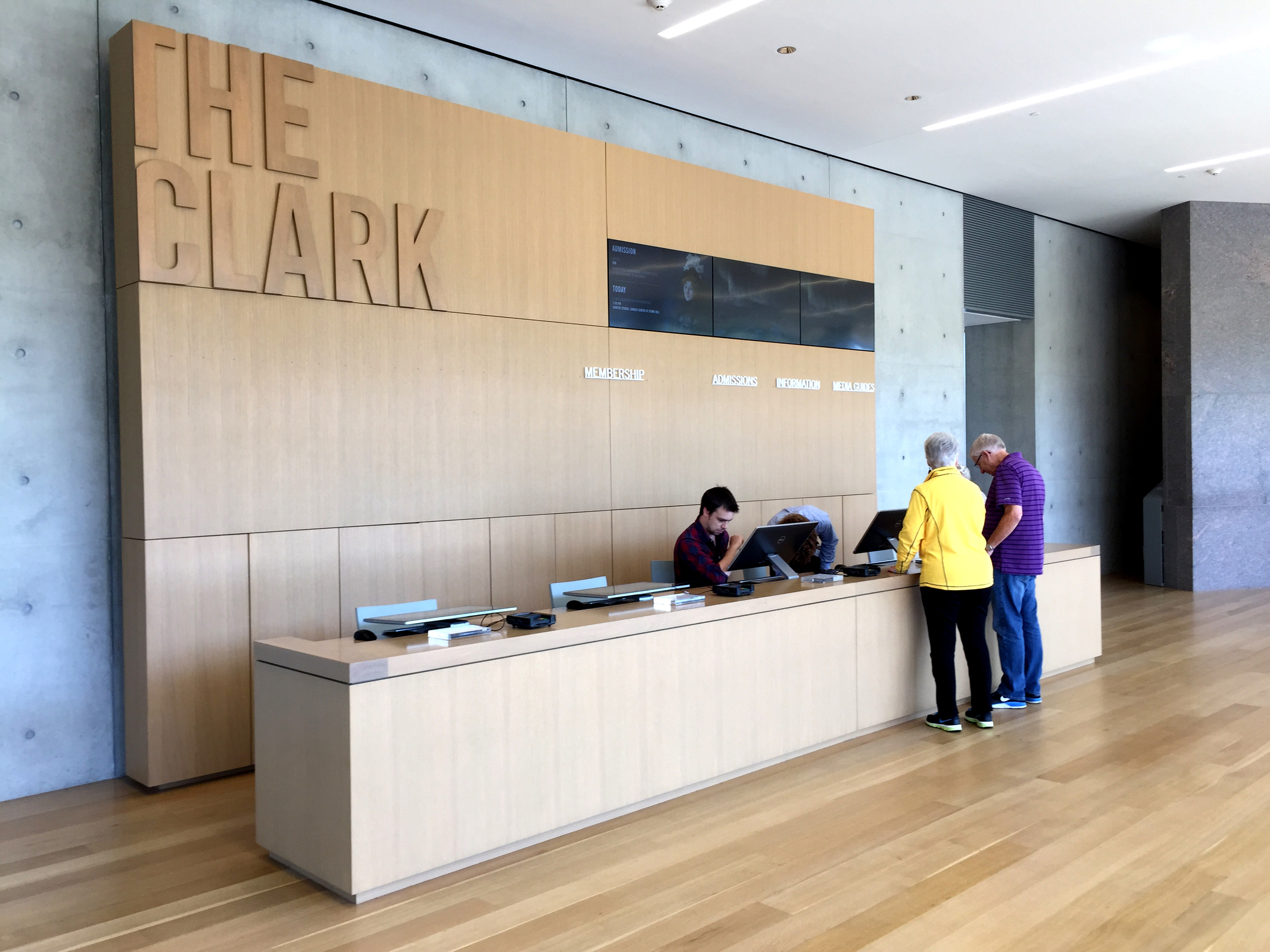 "The neutral language of rectilinear and horizontal planes continues throughout the building. A beautifully designed welcome desk embodies the language of the evolved museum:  the former Sterling Clark Institute now known simply as ""The Clark"""