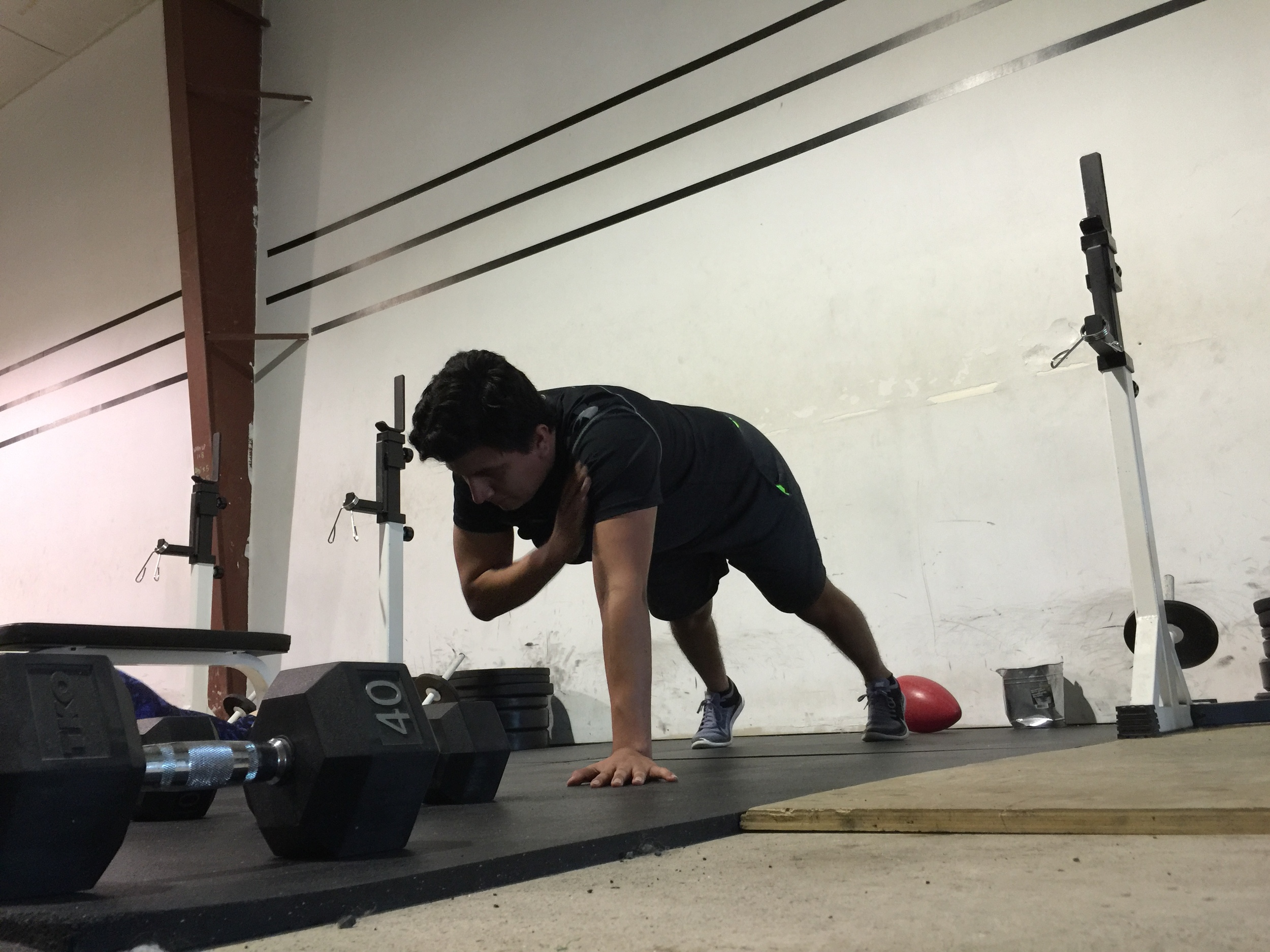 Jose holding a good plank position while performing shoulder taps.