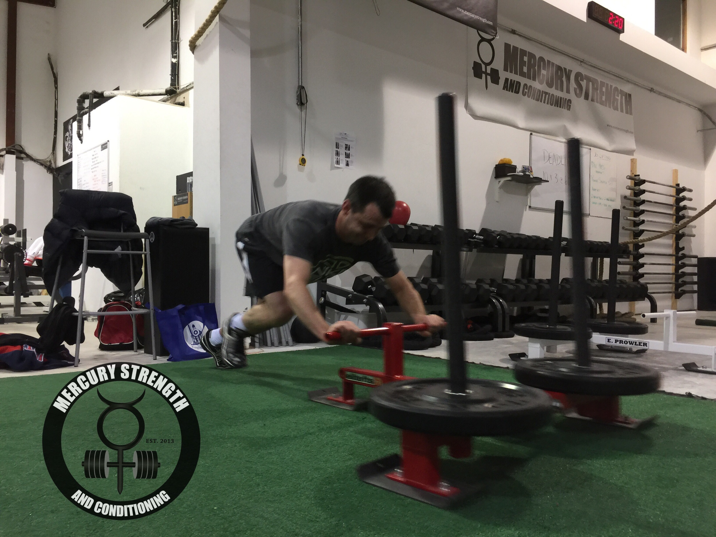 Nick pushing the prowler back to the starting line before some jumping lunges.