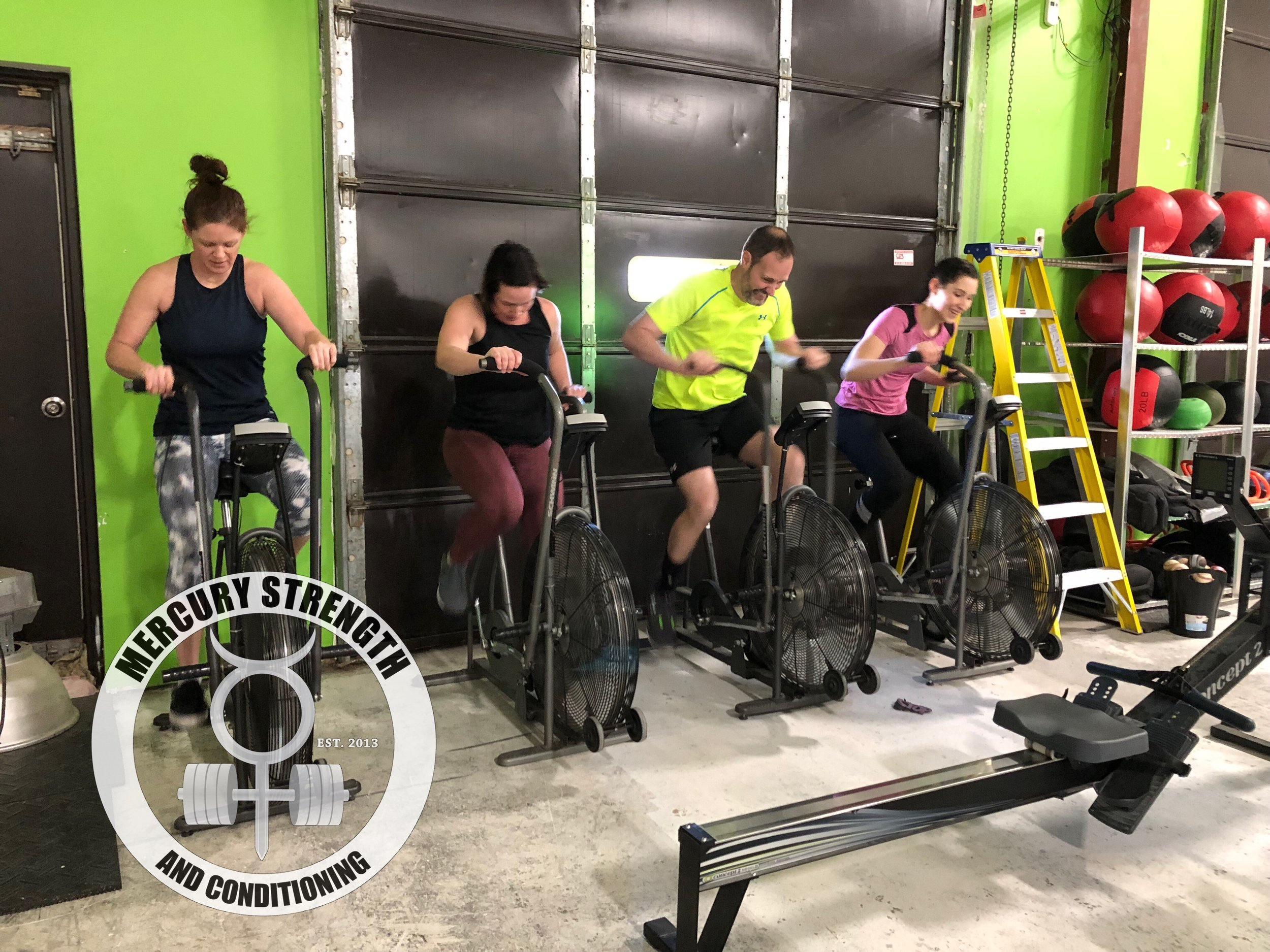 Cari, Lindsey, Andrew and Mel (I don't know why she's smiling on the air dyne) with some air dyne sprints during Saturday's workout.