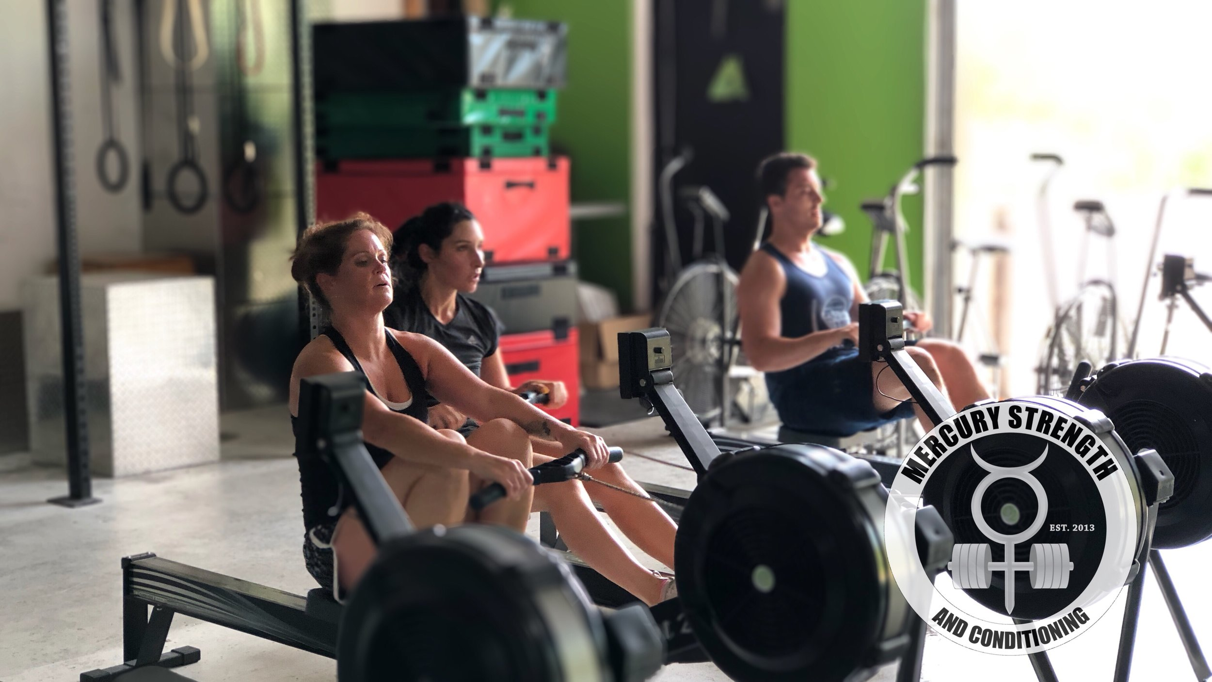 Cari, Mel, and Eddy pushing out a 2k row with burpees thrown in the mix