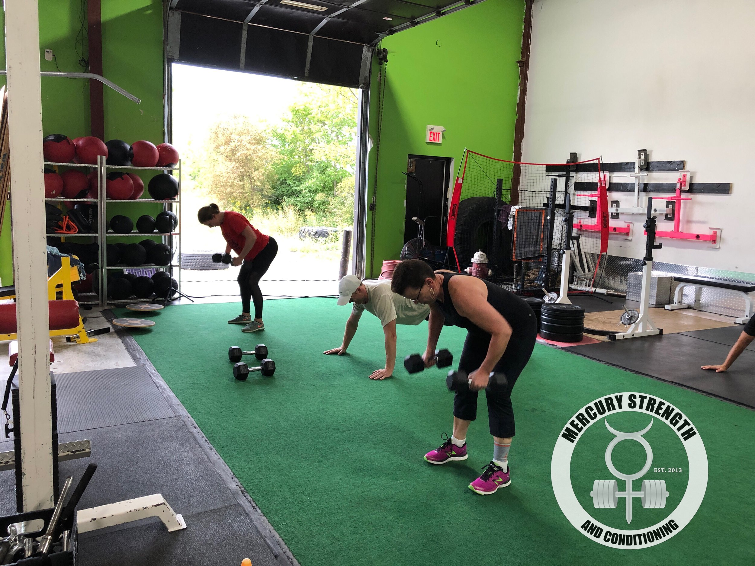 Alyssa, Kevin, and Evette grinding through a gruelling upper body workout.