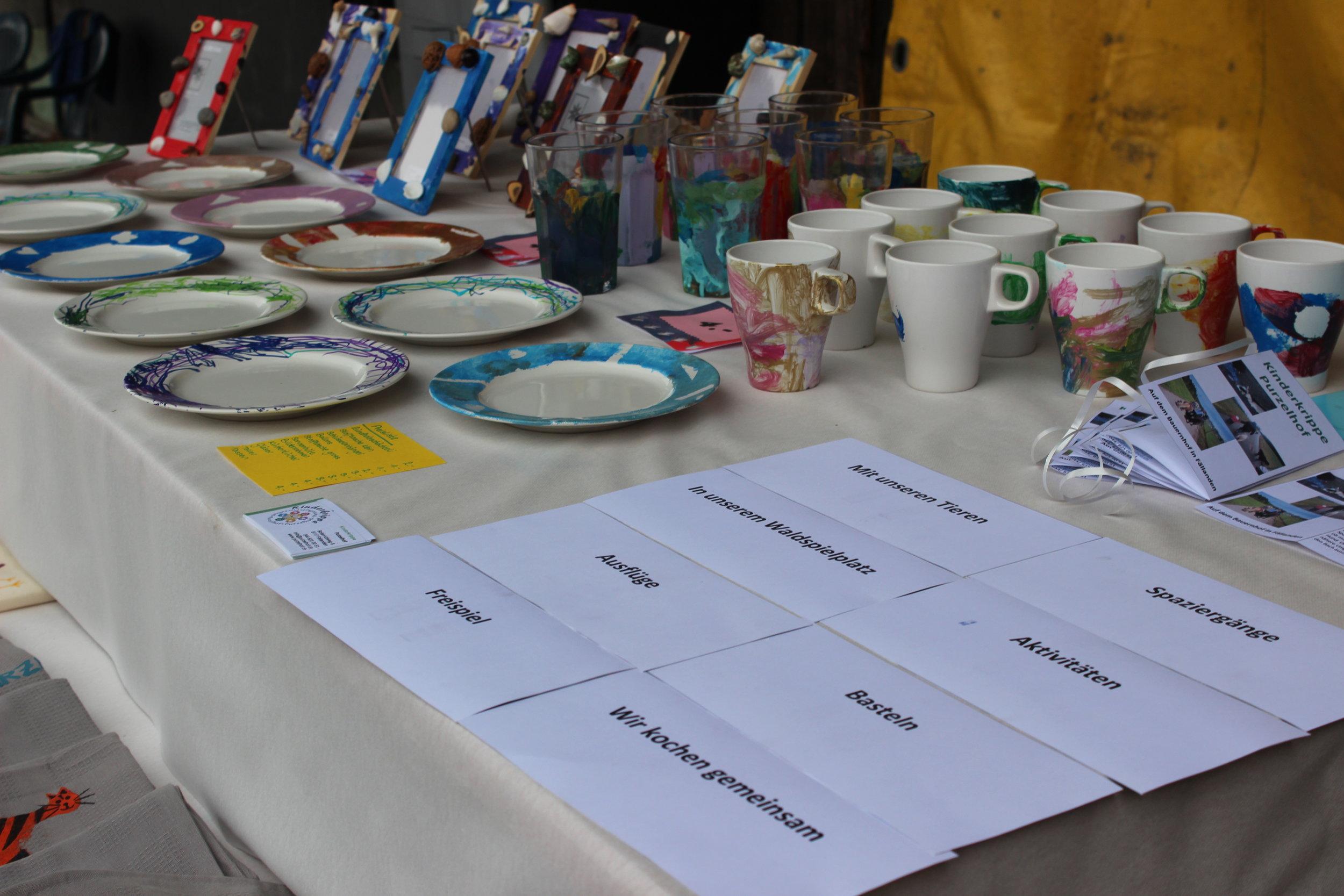 Ein Tisch mit gebasteltem der Kinder. - Teller, Tassen, Bilderrahmen, Stofftaschen, Sommerhüte, Schlüsselanhänger, Küchentücher und mehr.