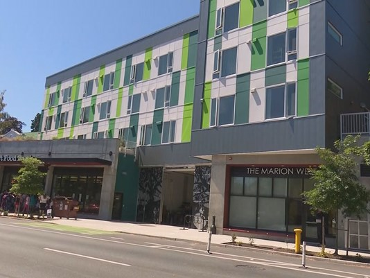 """""""An affordable housing property is getting some national attention for its innovative design.  http://www.king5.com/mobile/article/news/local/innovative-affordable-housing-design-for-homeless-youth-workers/458032254   The Marion West is a mixed-use affordable housing property in the University District that won two Gold Nugget Grand Awards at the 2017 Pacific Coast Builders Conference, including """"Residential Housing Project of the Year"""".  The Low Income Housing Institute (LIHI) and Runberg Architecture Group collected the awards in San Diego.  The Marion West's 2nd floor is dedicated to 20 units of permanent supportive housing for formerly homeless youths. This means they are given some wraparound services like an on-site case worker. Residents pay whatever 30% of their income is. The nonprofit YouthCare runs the floor.  The 3rd and 4th floors are 29 units of workforce housing. Units cost residents $640 per month, according to Sharon Lee of LIHI.  The 7,400 square foot rooftop has an urban garden residents can use. The rooftop also has downtown Seattle skyline views.  Downstairs houses the University District Food Bank. Some of the rooftop garden provides fresh produce for the food bank. Also downstairs, Street Bean Coffee is an apprentice program for formerly homeless youth.  The building cost $15 million for the land purchase and construction, said Lee.  """"Really it's about the culmination of all those uses put together that create this synergy of this space,"""" said Brian Runberg, principal at Runberg Architecture Group.  William Sandoval has only lived at The Marion West a couple of months, but it already is starting to feel like home to him.  Sandoval, who's on Social Security, said he used to live in motels.  """"I've paid as much as 90 percent of my social security income per month in these hotels,"""" said Sandoval, describing life as 'survival mode.'  """"Now I have the ability to buy clothes, buy my own food and in a sense feel viable again as a human being which is r"""