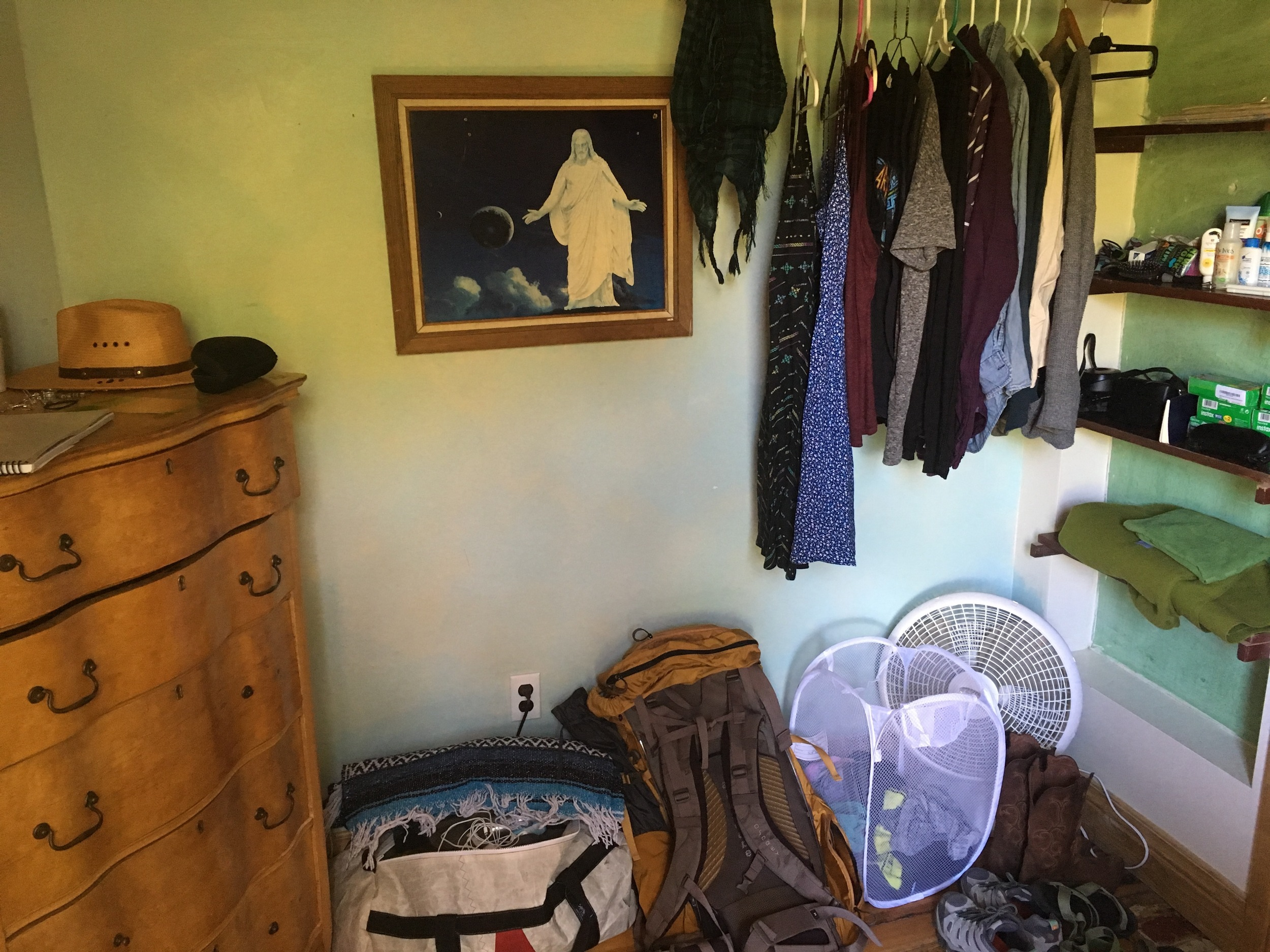 Under my loft bed: dresser and clothes rack (and picture of Jesus in space?)