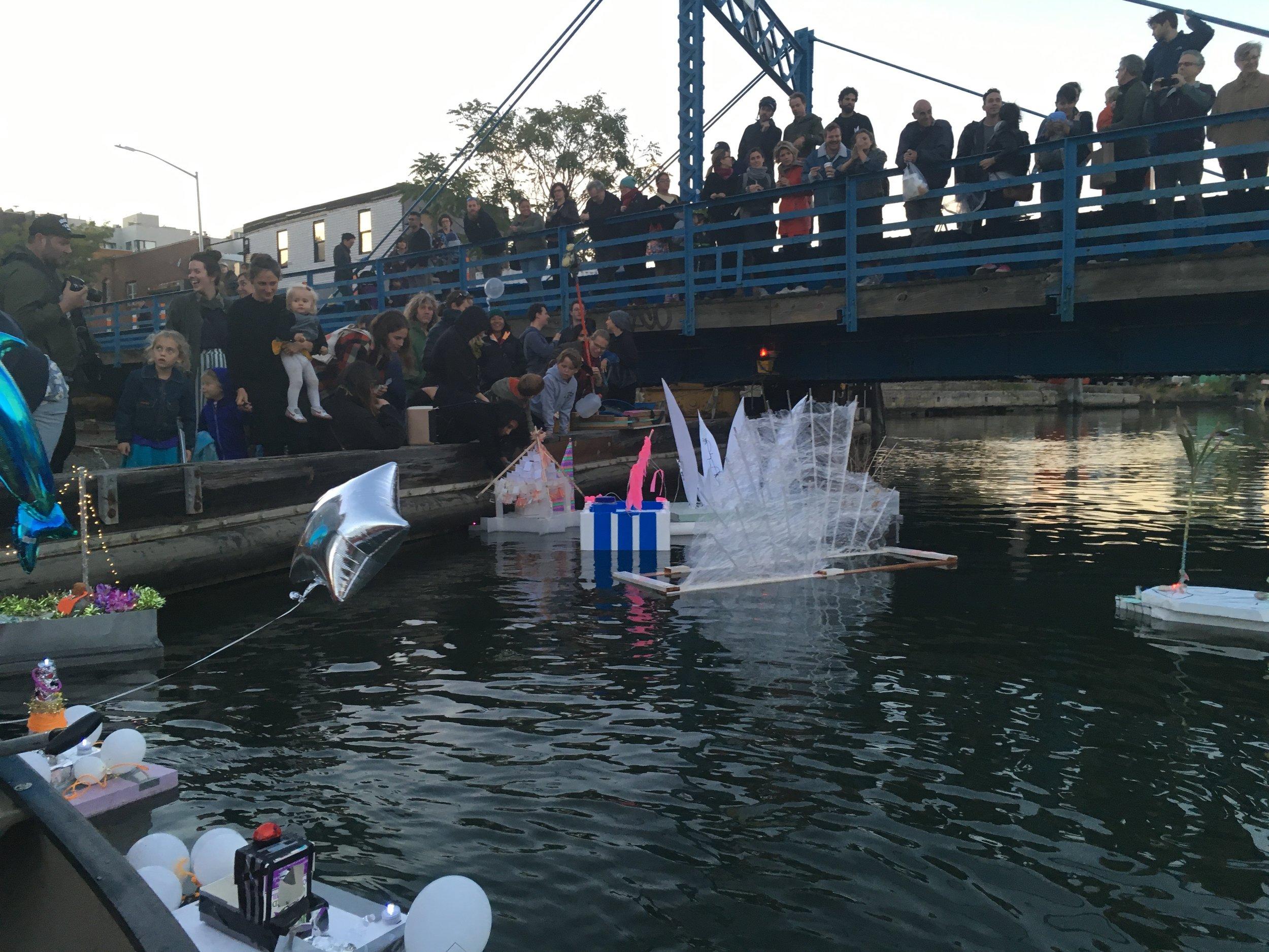 A crowd gathers on a bridge overlooking the Gowanus art flotilla.