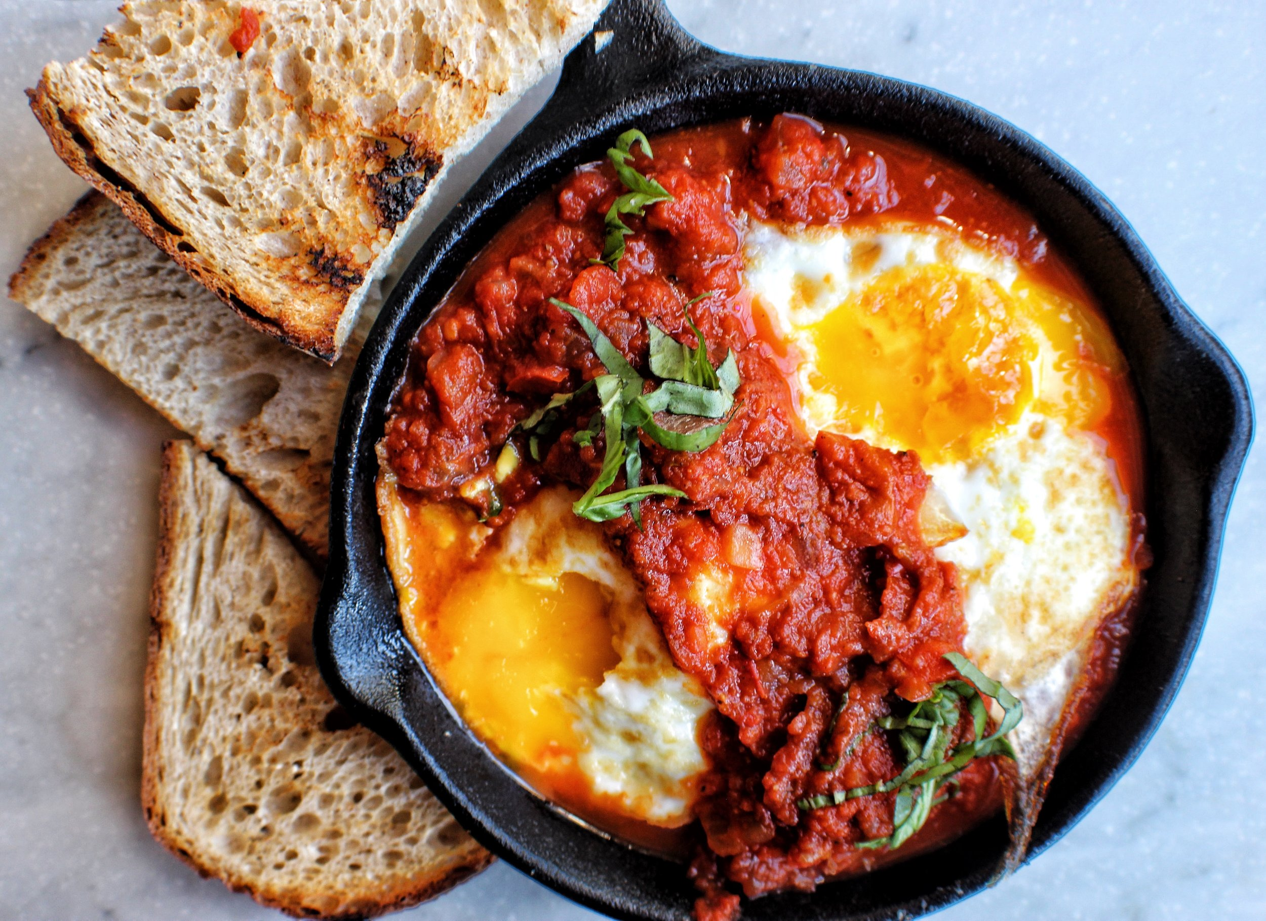 Mediterranean eggs -  two eggs, homemade tomato, pepper & onion sauce with Mediterranean spices & grilled bread