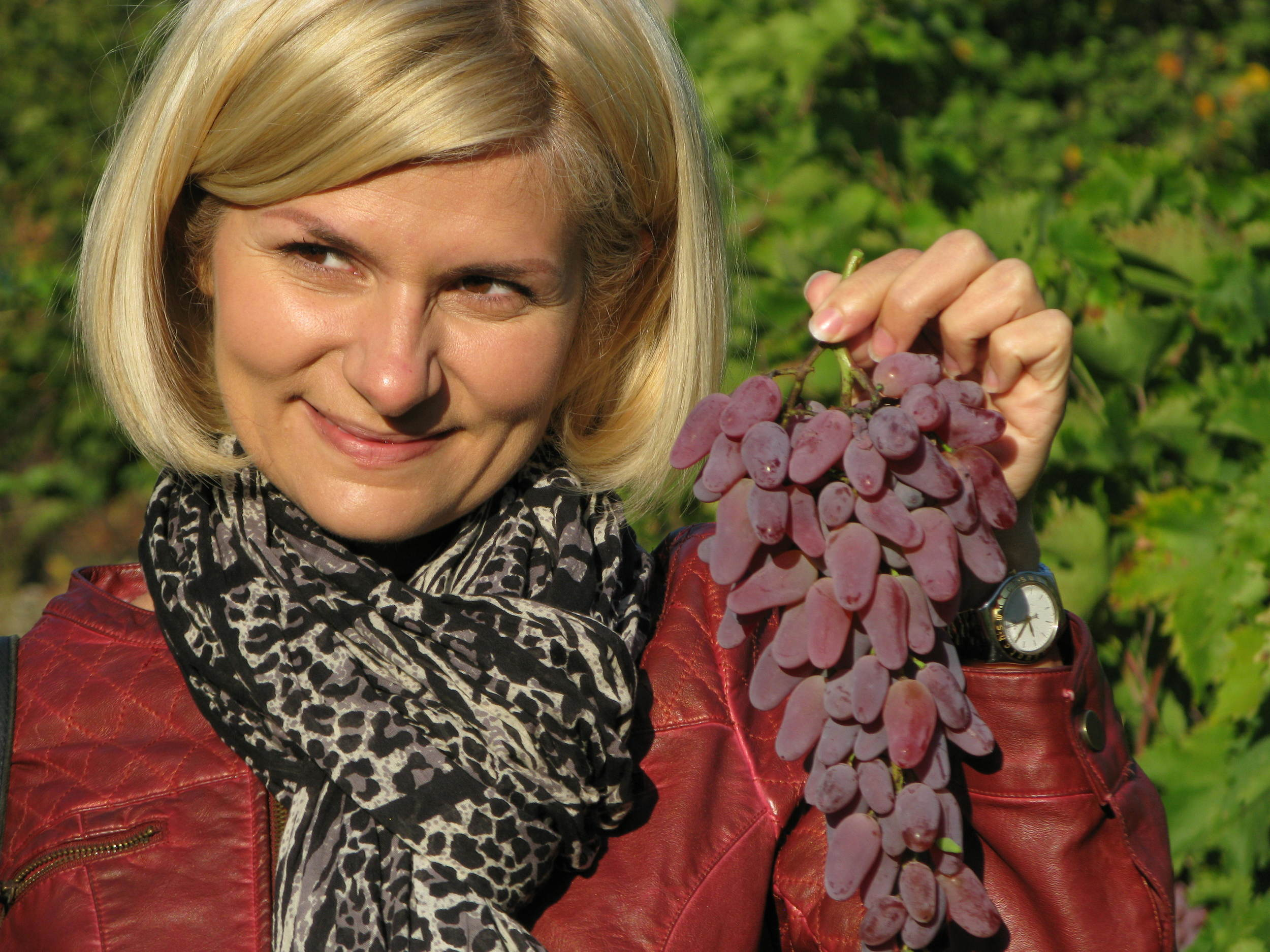 Natalia Shows Off the Strange Shape of the Grapes for the Homemade Wine