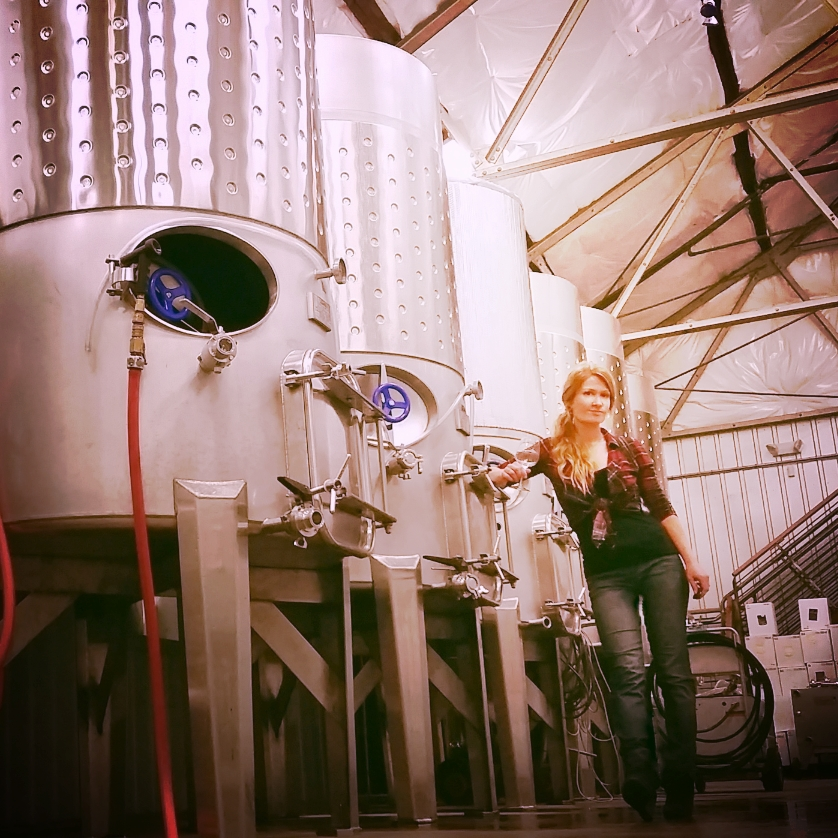 Lauren Y. Zimmerman standing beside 600 and 1100 gal tanks at Port of Leonardtown Winery.