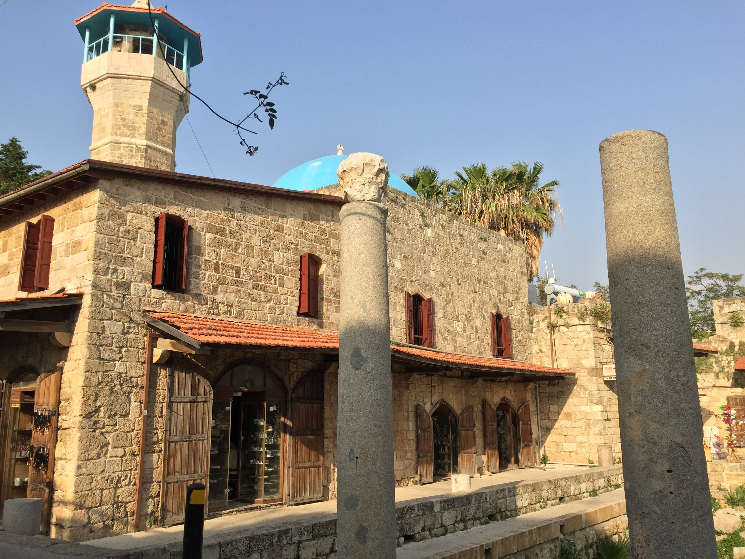 A tiny mosque stands next to ancient Roman pillars in Byblos