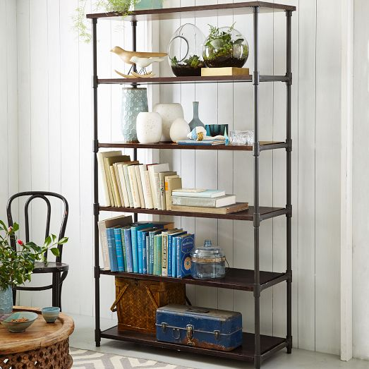 Vintage pieces, florals and collections make a pretty display with books on this West Elm pipe bookcase. Photo: West Elm