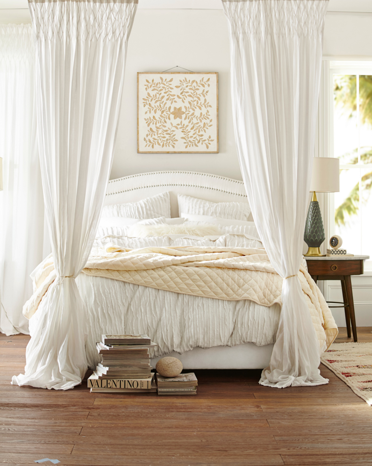 Dreamy bedding inspires peaceful sleep in this bedroom using creams and whites for a calm effect. A fabric headboard, layered strips of fabric keep the overall effect light and airy. Camille duvet cover and sham from Pottery Barn. Photo courtesy of Pottery Barn.