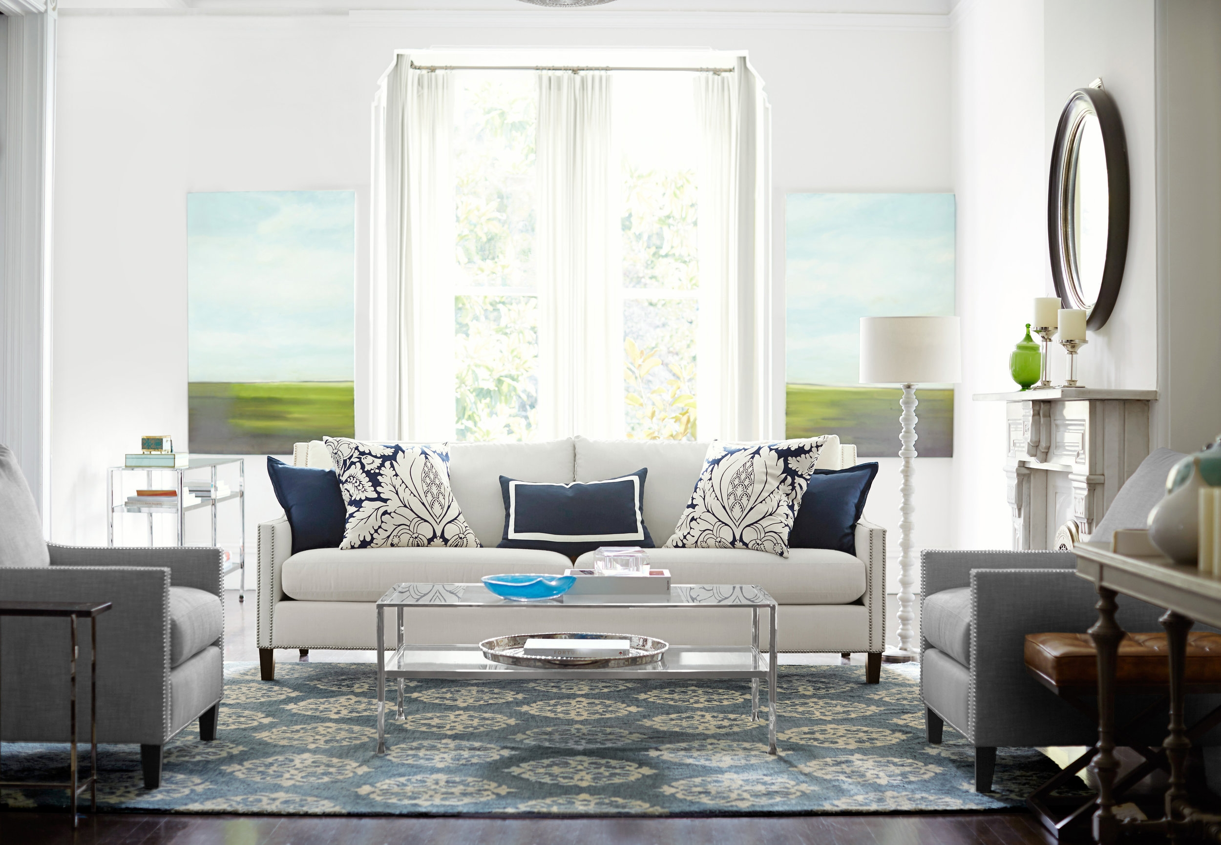 Contemporary and traditional empire scroll rug has the look of an antique time-work work of art and ties this room together as it fits under legs of chairs and sofa. Notice the pillows, pair of paintings and pair of chairs that also make this room cohesive. Photo courtesy of Pottery Barn.