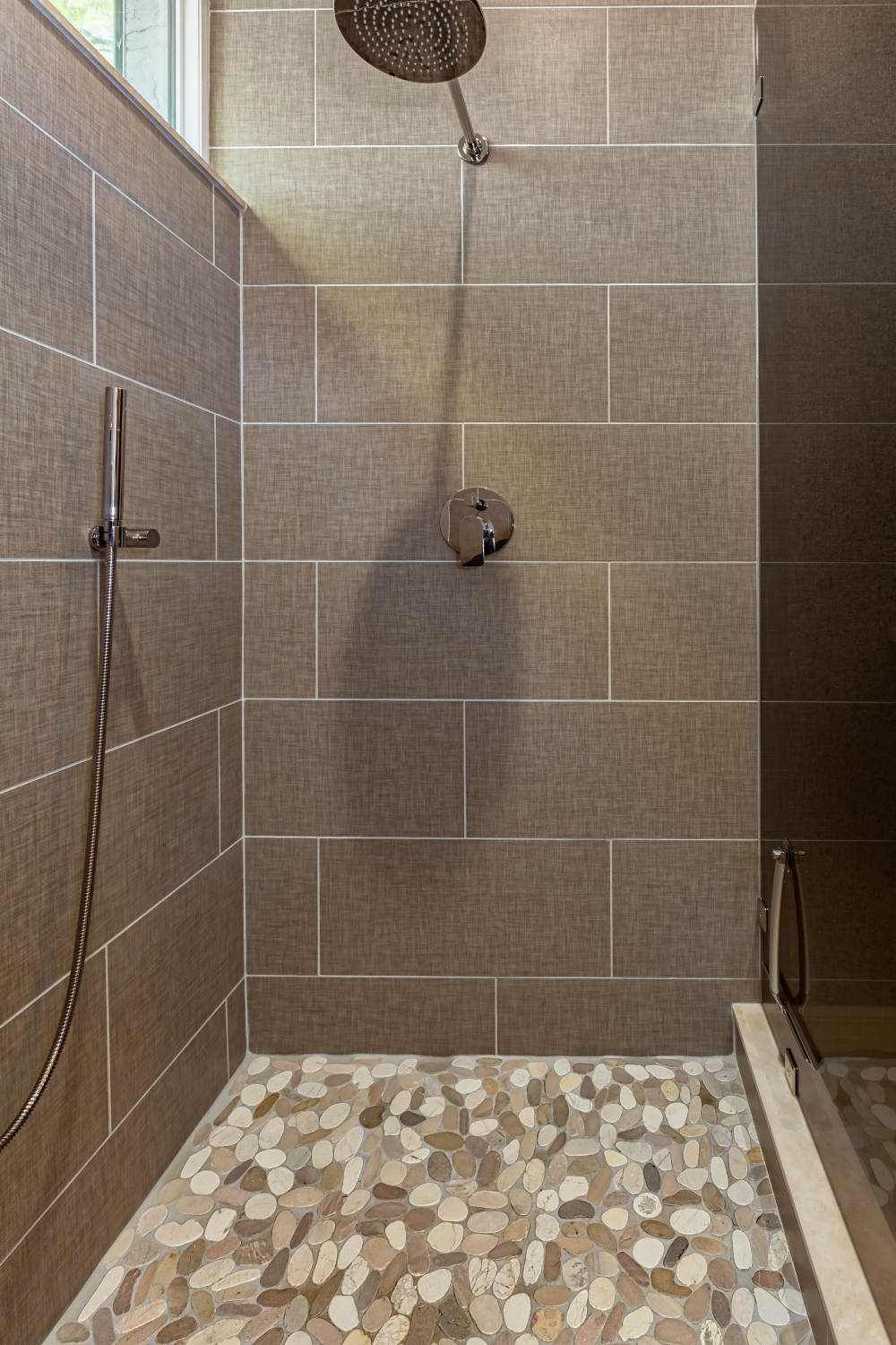 In addition to the rain shower, a hand-held shower is great for cleaning and for showering pets and kids. Flat pebble flooring and linen finished tile on walls. All photos by R.L. Caron. Courtesy of Diane Torrisi Designs.