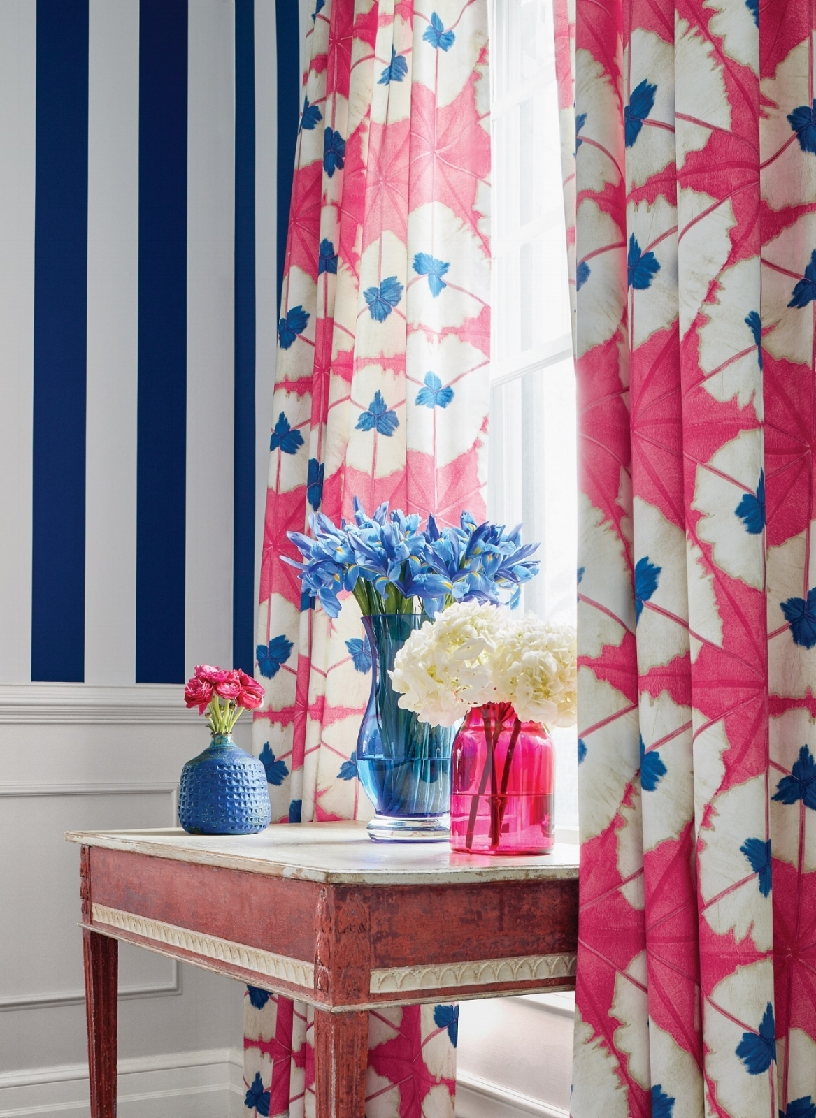 Color changes everything with Thibaut Design's  Summer Stripe  wallpaper in navy paired with  Sunburst  printed fabric in pink and blue.  Photo: Courtesy of Thibaut Design.