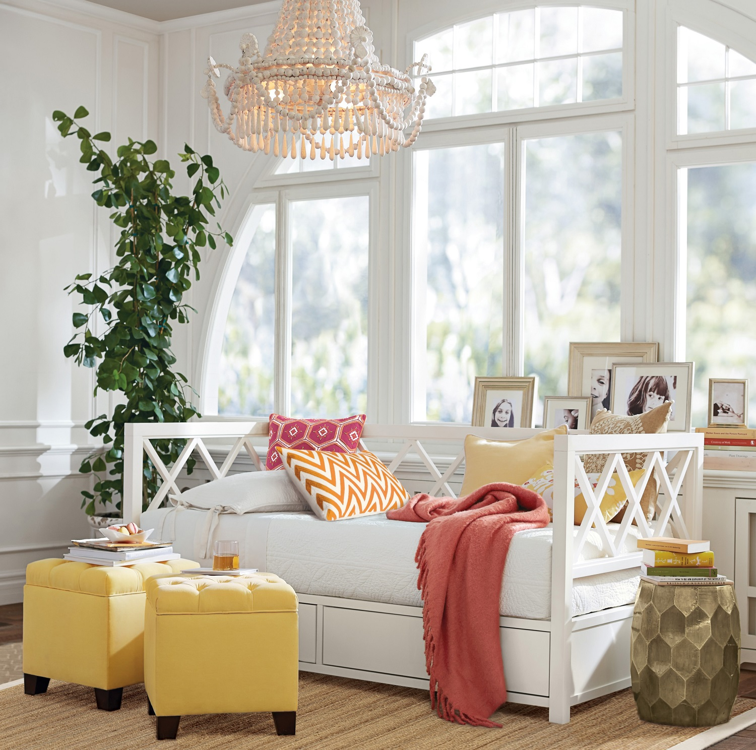 Yellow accents such as throw pillows, Lorraine tufted storage cubes, Venice metal-clad accent stool, pillows and books are beautiful in this white room with Pottery Barn's Clara Lattice Storage Day Bed. With the coral throw, this is a pretty color palette that works well with yellow. Photo: courtesy of Pottery Barn.